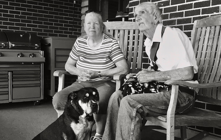 Trained service dog sitting with seniors.